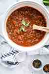Large pot of spaghetti bolognese with herbs and a wooden spoon