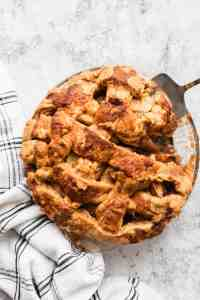 Easy apple pie in a glass pie plate with a slice being lifted out