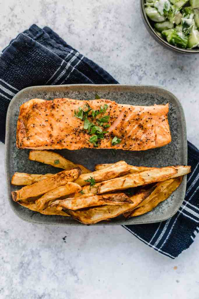 Air Fryer salmon on a plate and a kitchen towel