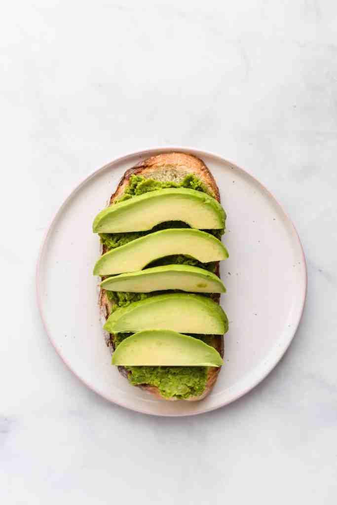 Avocado slices on mashed peas on toast
