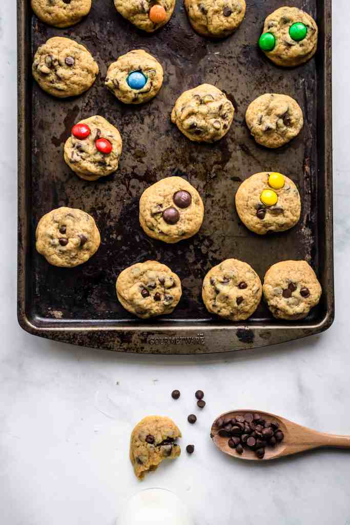 Distressed baking sheet with mini chocolate chip cookies cooling on it and a wooden spoon with chocolate chips on it
