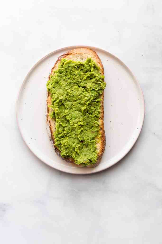 Smashed peas on sourdough bread on a plain plate