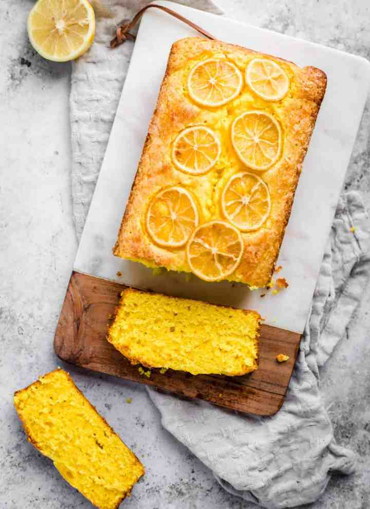 Lemon turmeric cake sliced on a chopping board with a kitchen towel