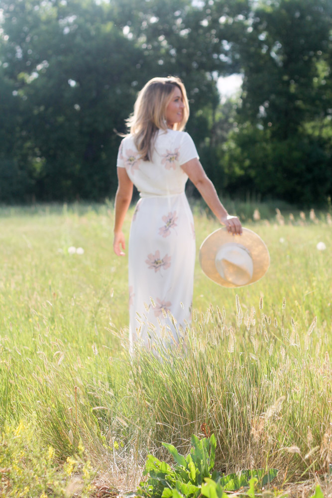 amber from every once in a style in a field wearing a white floral print wrap maxi dress