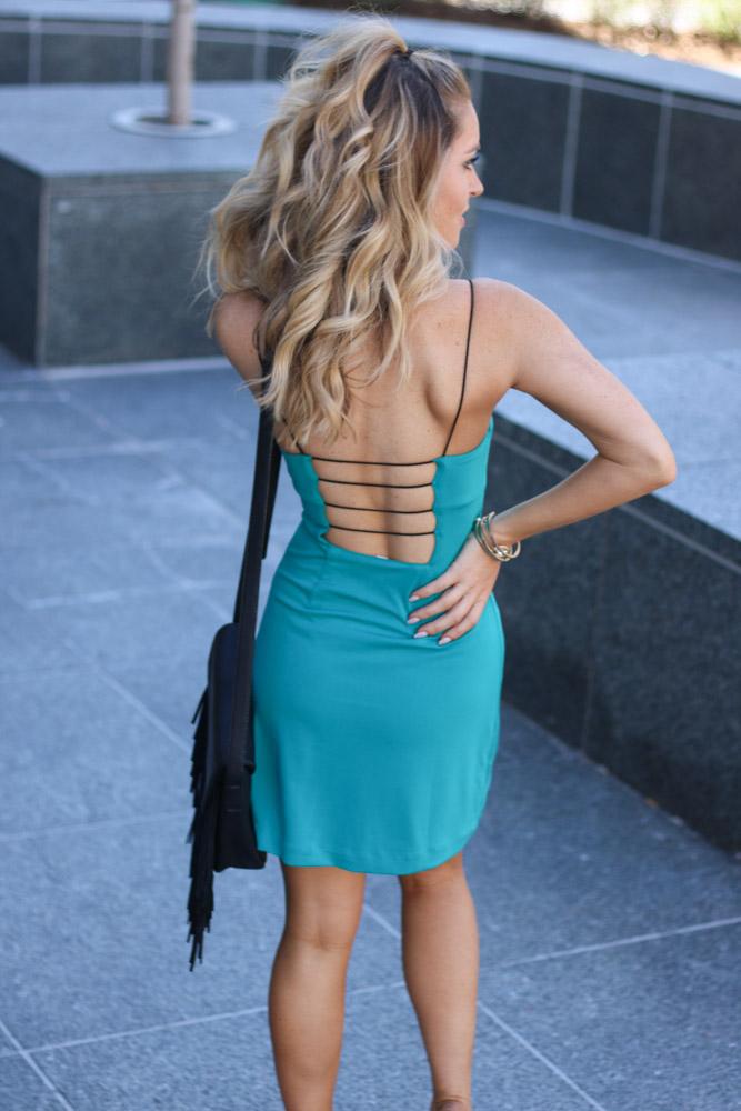 teal green mini dress with a black fringe bag