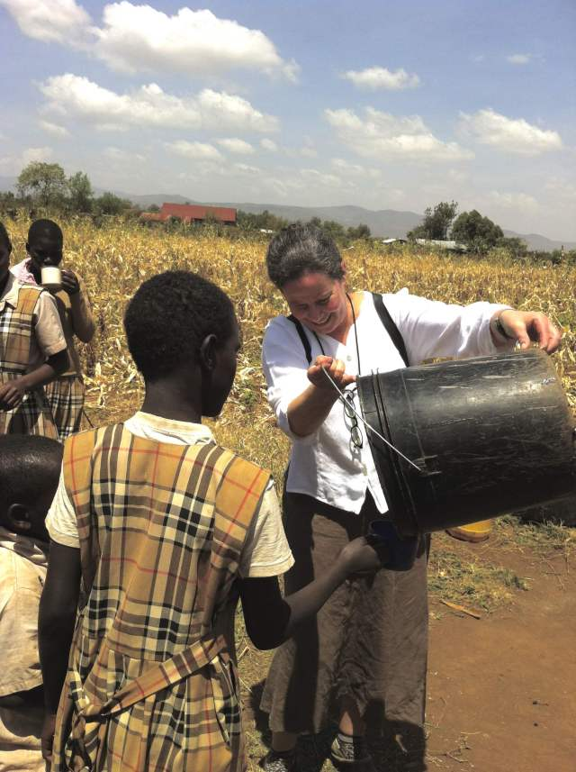 an American teacher caring for a child in Kenya