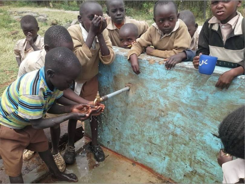 children drinking from a spigot in sub Saharan Africa