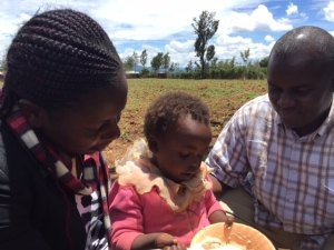 providing for needs: two adults give a meal to a child in Kenya