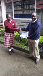Alice receiving her certificate of completion from William Aludo