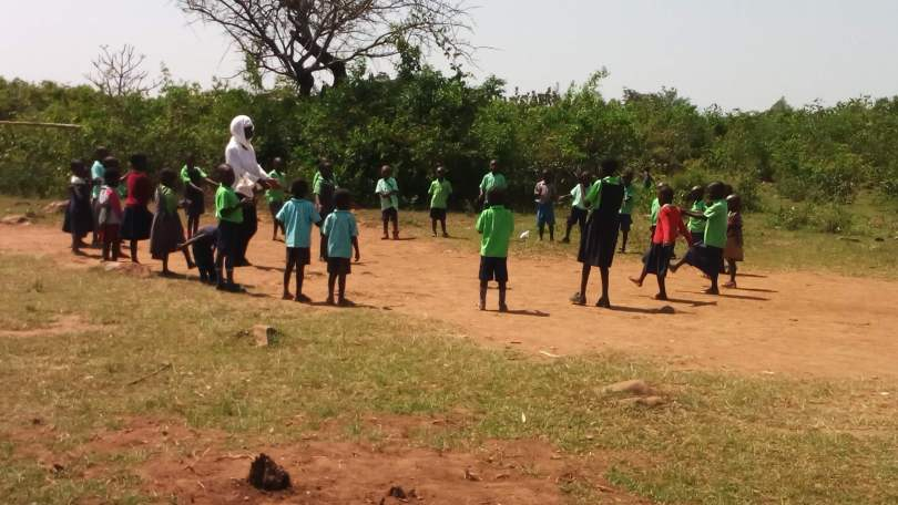 Children playing outside with their teacher at Miruya Primary School in Kenya