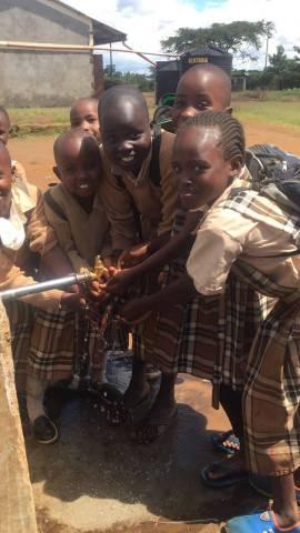 Kenyan school children getting maji (water) from a faucet