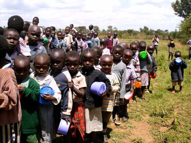 a group of children holding bowls and waiting for food in Kenya