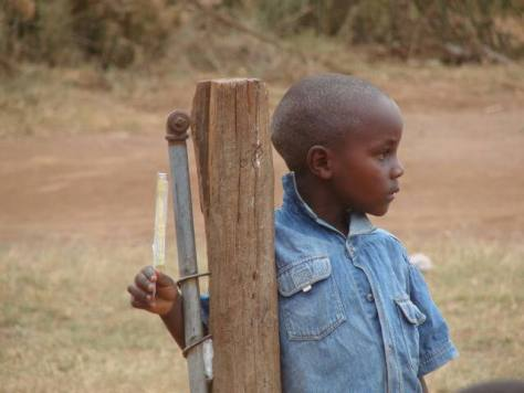Providing scholarships for children who have lost one or both parents, such as this lone child by a post