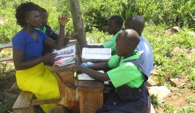 Teacher & children learning under a tree