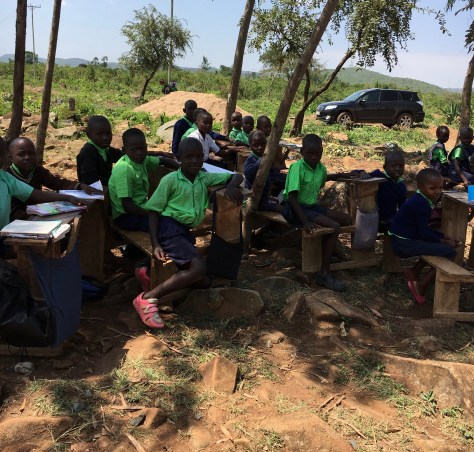 Everyone's Child students sitting at desks outside at Miruya Primary School