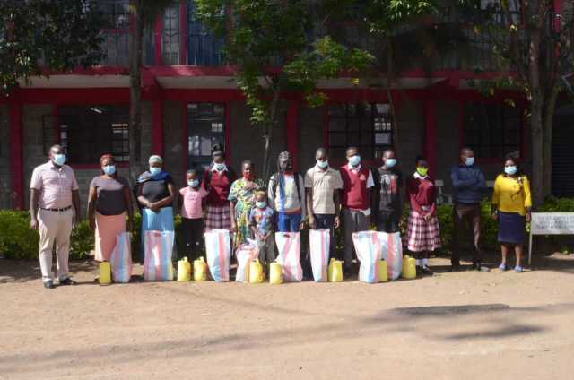 A group of 8 students at Bishop Donovan Secondary School in Kenya with bags of food