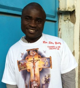 An update to the story: Simon Wanjala in front of a blue door with a big smile