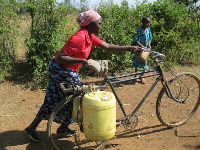 woman retrieving water on a bicycle
