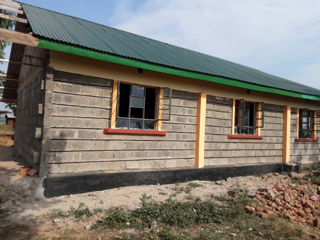 Outside the new stone classroom with a green metal roof and orange casings around the windows