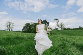 Bride running down the hill as fast as she can without falling over