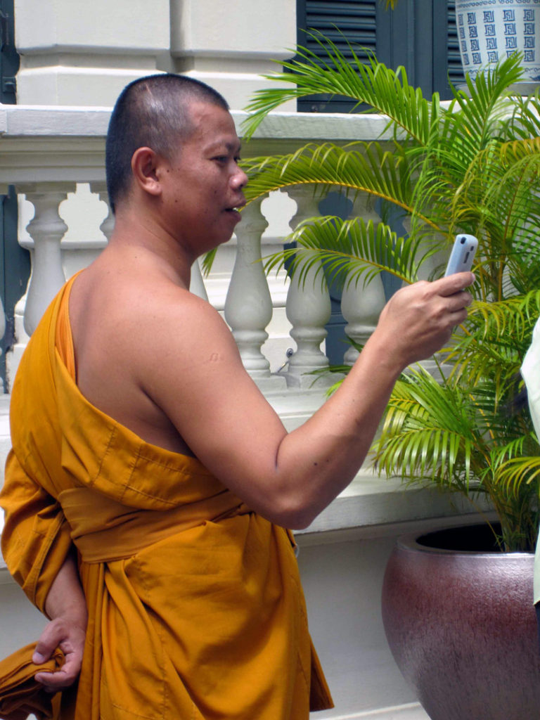 a monk and his iphone in bangkok, thailand