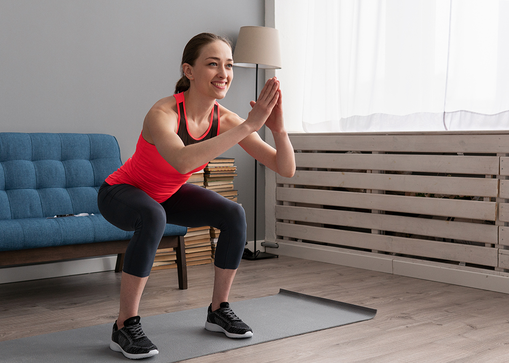A woman working out at home, performing bodyweight squats over an exercise mat in her living room.