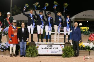 The winning team from Great Britain, including Ben Maher, Emily Mason, Emily Moffitt, Chef d'Equipe Di Lampard, and Amanda Derbyshire with ringmaster Steve Rector, Woodward Middleton, Jr., Managing Director of U.S. Trust Bank of America Private Wealth Management, and Michael Stone, Equestrian Sport Productions President.