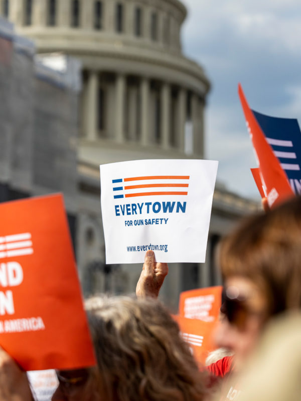 An Everytown sign is raised in a crowd in front of the Capitol