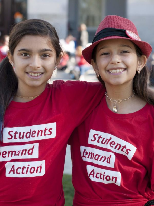 Two young girls smile while wearing Students Demand Action t-shirts