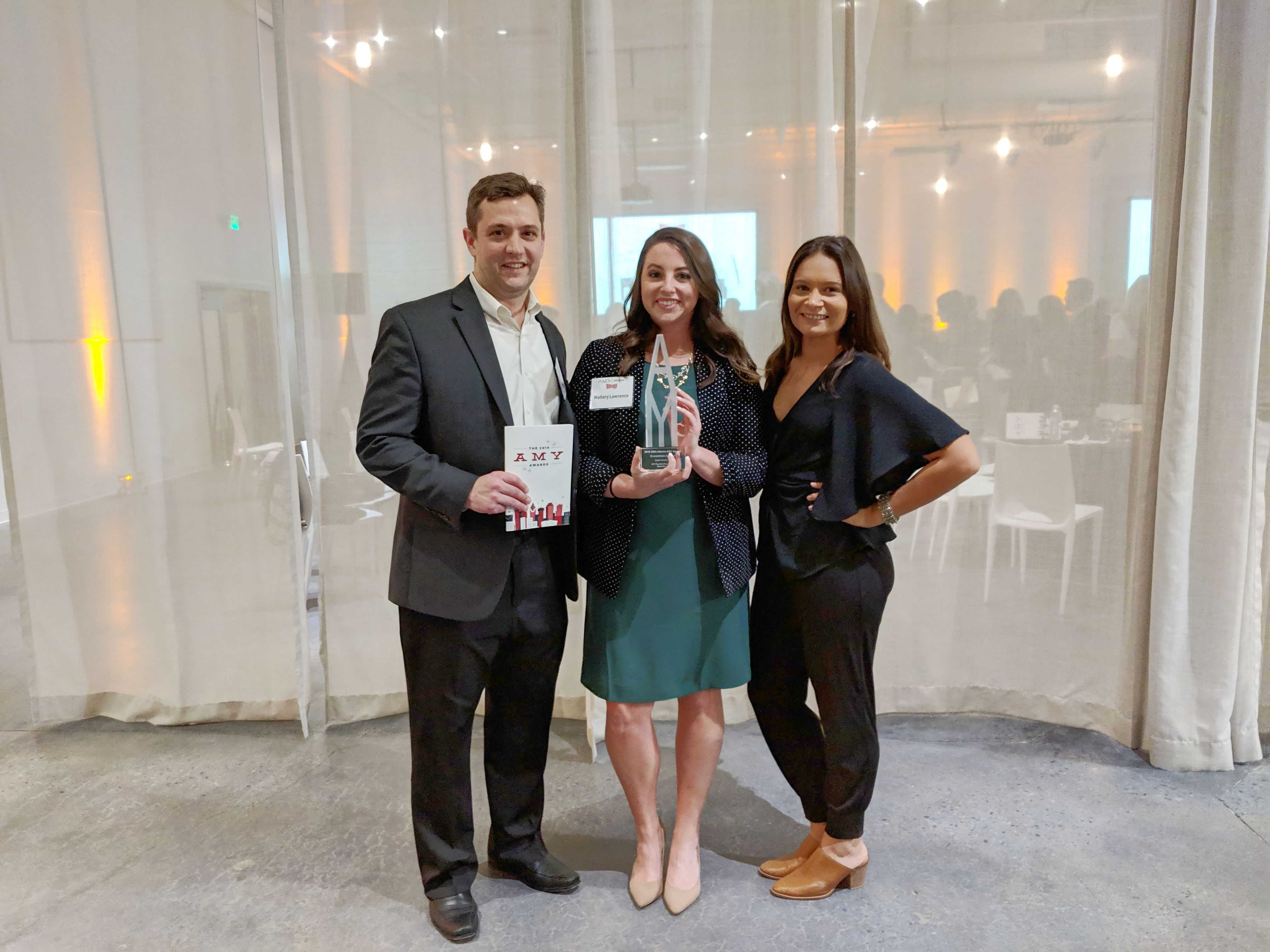 """Holding Amy's 2019 """"Best Digital Advertising Campaign"""" trophy"""
