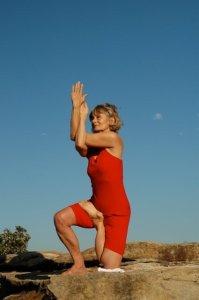 Eve doing kneeling yoga pose on a rock.