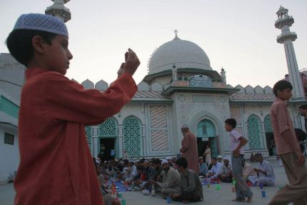 Boy outside mosque waits for evening Ramadan prayer