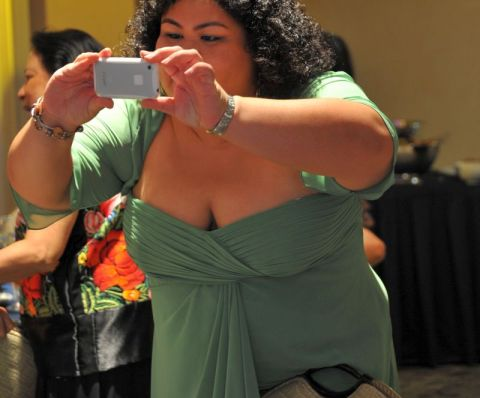 Large woman taking photograph