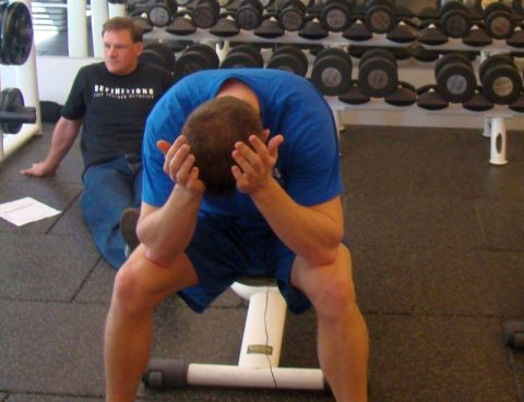 Exhausted man sitting on weightlifting bench