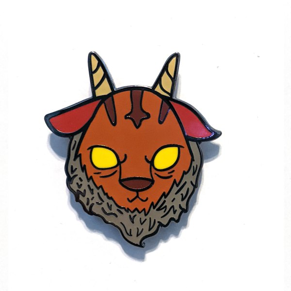 A photo of a enamel pin of a goat-devil mashup
