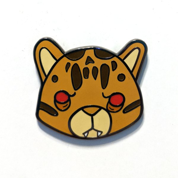 A photo of an hard enamel pin of a cute were-leopard named Leopold