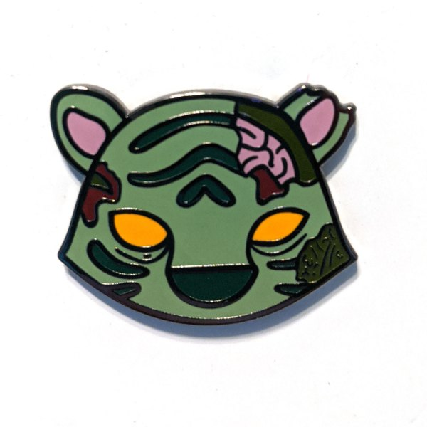 a photo of an enamel pin of a cute, greenish zombie tiger with orange eyes