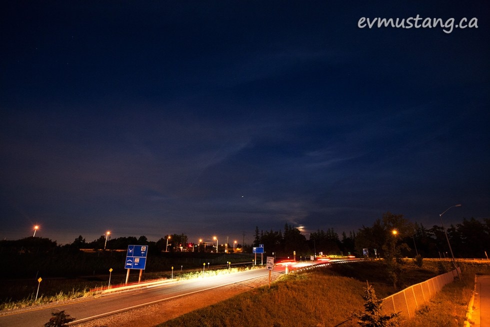 long exposure image of the turn off to milton from the 401 ontario highway with rising moon and clouds