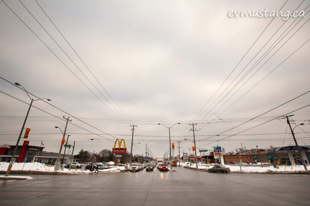 image of the intersection of lansdowne and the parkway in peterborough, ontario on a cloudy day three days before christmas showing stopped taffic at the lights waiting to drive toward the viewer