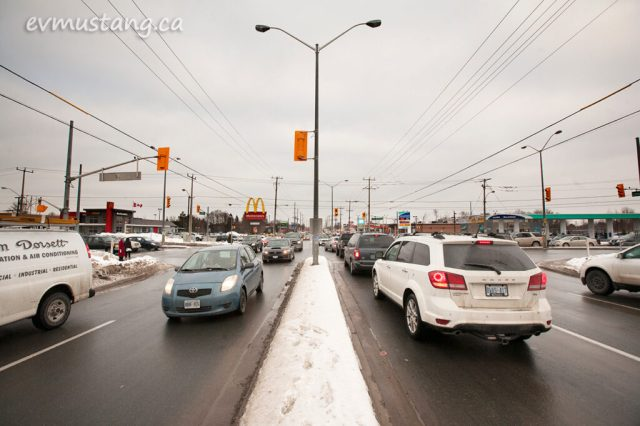 image of the intersection of lansdowne and the parkway in peterborough, ontario on a cloudy day three days before christmas showing taffic and lights and snow