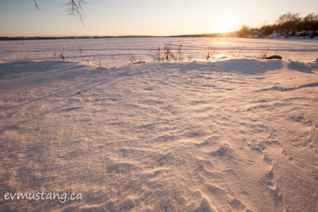 image of cold hardened snow drifts with sunset in distance