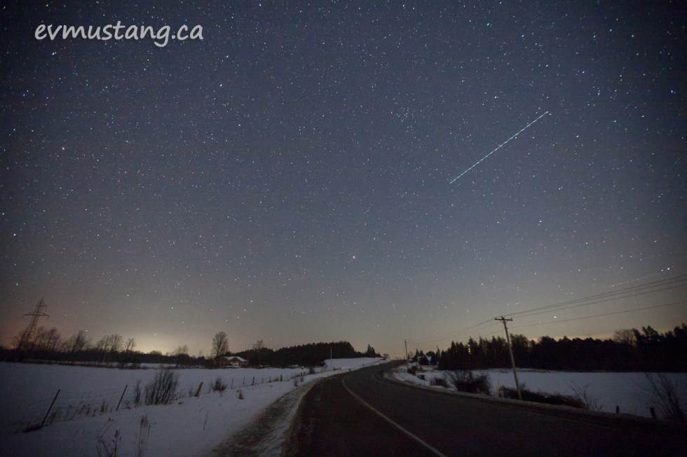 image of starfield and trackline of jet lights over a night road