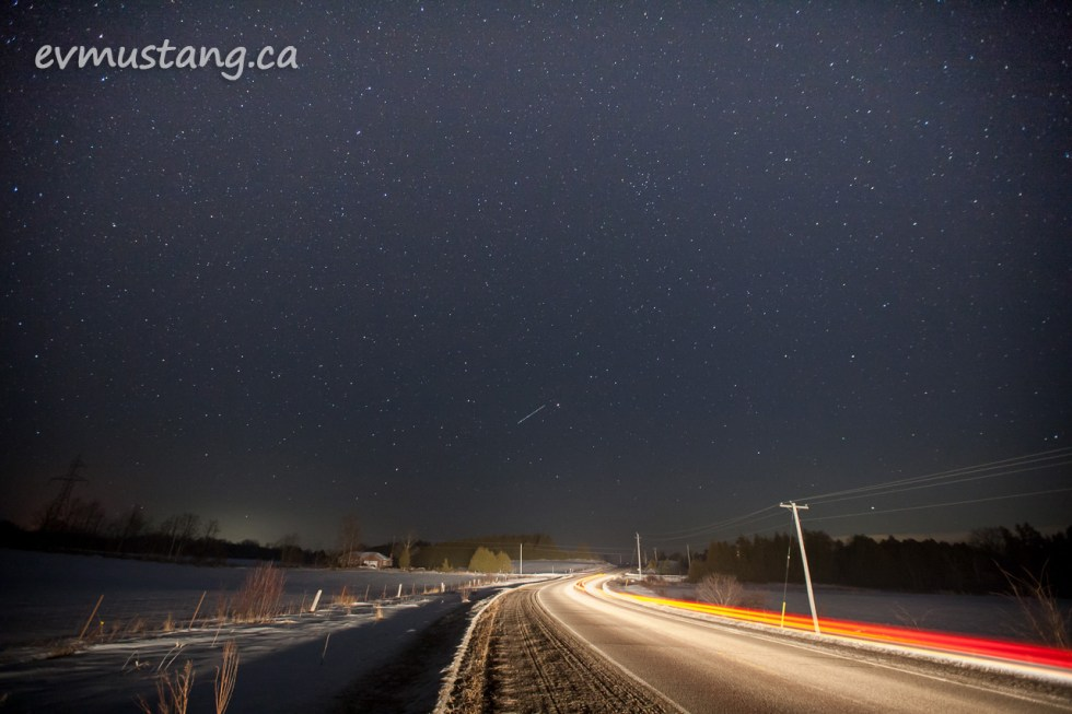 image of nighttime roadway with stars and tail lights