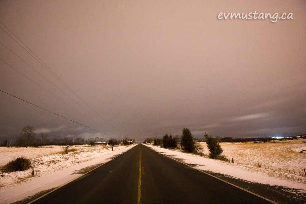 image of a country road at night under a light blanket of snow