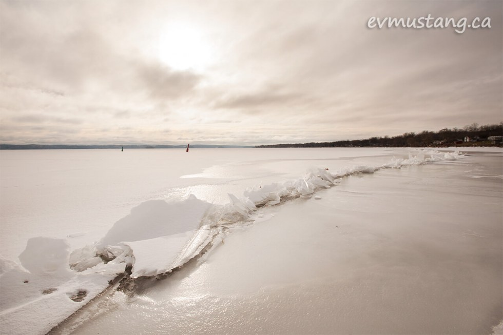 image of a jagged ice shelf pushed up through the surface of rice lake under a glowing, cloudy sky