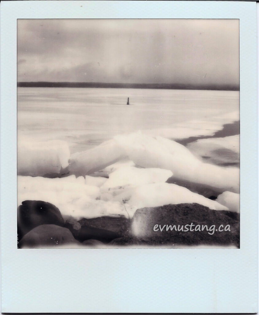 scan of a black and white polaroid of a buoy trapped in ice in a lake