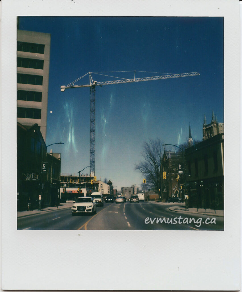 scan of a polaroid of a crane reaching over richmond street in london ontario