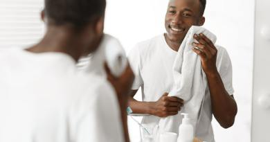 Black Man Wiping Face With Towel After Shaving In Bathroom
