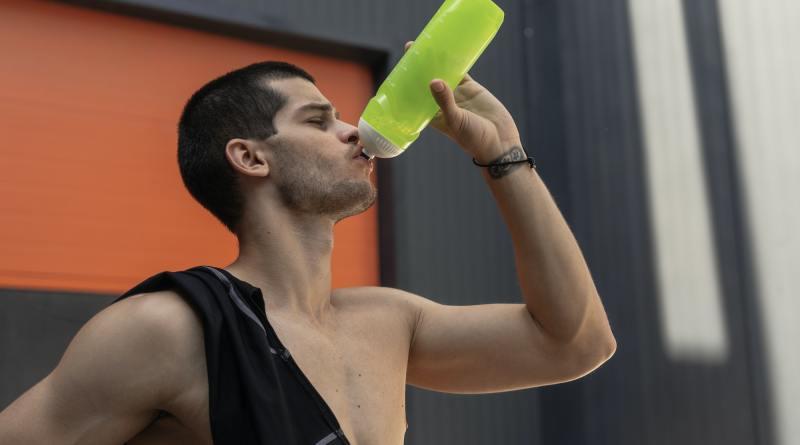 Close-up portrait athletic sportsman drinking watter