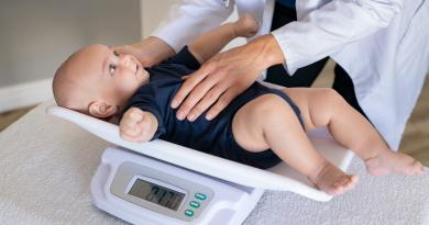 Doctor weighing baby